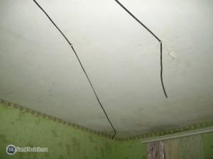 Прокладка кабеля по потолку, кабель справа - под люстру, слева - входит в гипсокартонную стену и опускается вниз к розетке.